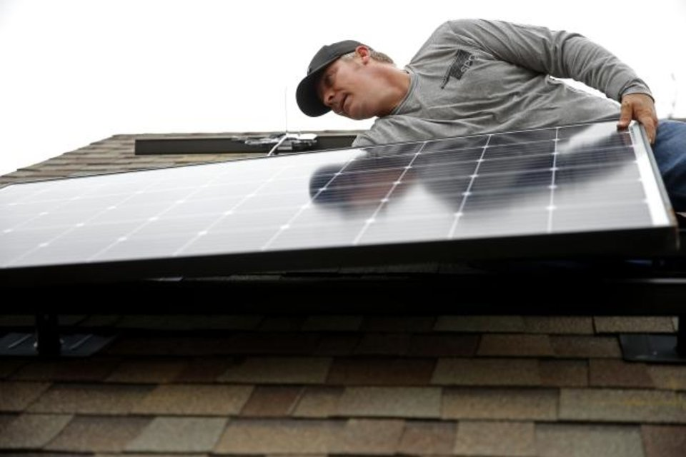 Photo -  Jeremy Rains, with Solar Power of Oklahoma, lines up a solar panel on the roof of Brian Bennett's home in Edmond. [BRYAN TERRY/THE OKLAHOMAN]