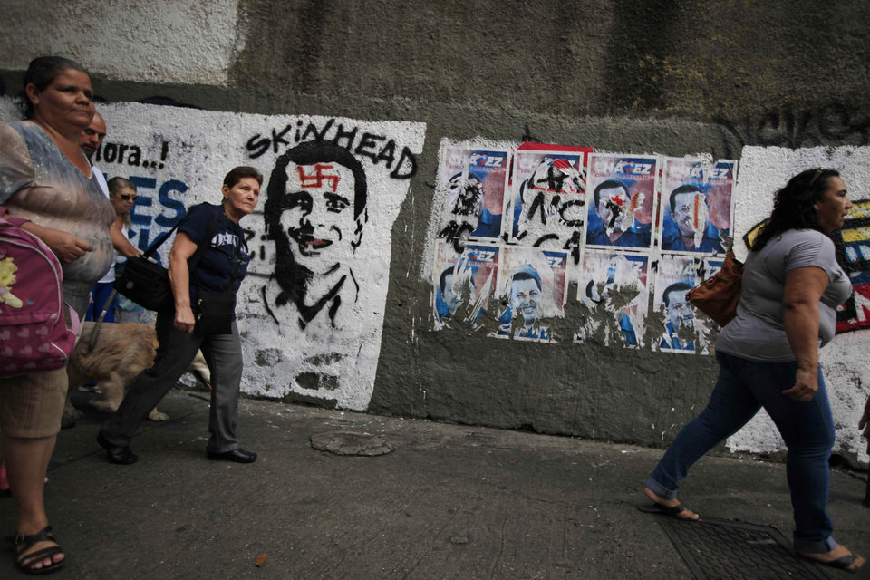Election posters supporting Venezuela's President Hugo Chavez, right, and a defaced mural of opposition presidential candidate Henrique Capriles, left, cover a wall in Caracas, Venezuela, Friday, Oct. 5, 2012. Venezuelans will head to the polls Sunday to vote in their country's presidential election, deciding on whether to keep Chavez or seek change with opposition candidate Henrique Capriles. (AP Photo/Ariana Cubillos)