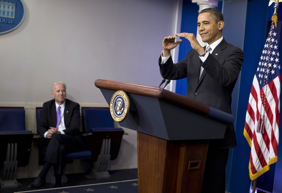 Photo - Vice President Joe Biden, left, listens as President Barack Obama gestures as he talks about the fiscal cliff negotiations during a news conference in the briefing room of the White House on Wednesday, Dec. 19, 2012 in Washington.  Obama also announced that Biden will lead an administration-wide effort to curb gun violence in response to the Connecticut school shooting. (AP Photo/ Evan Vucci)