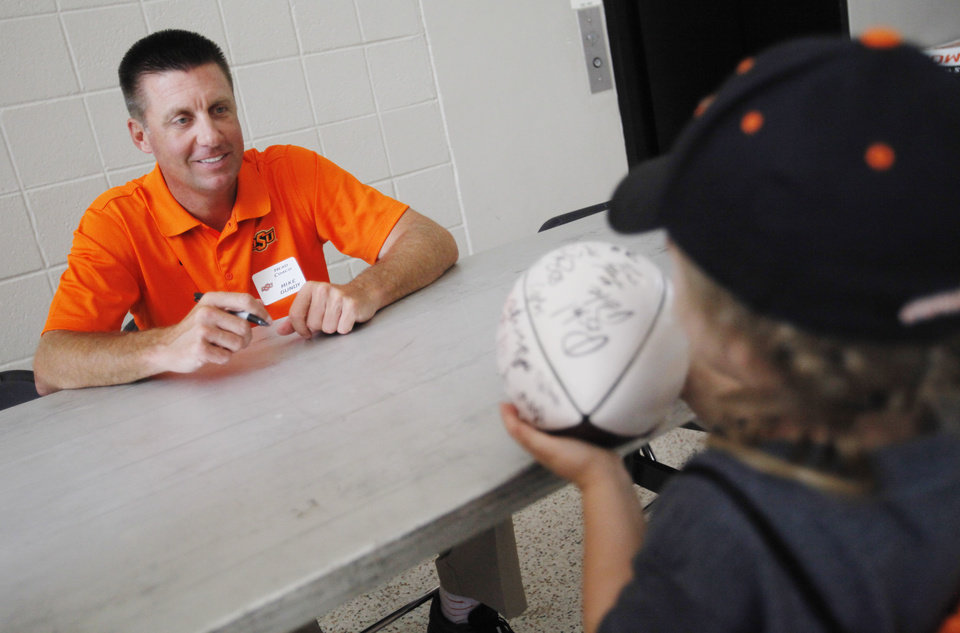 Photo - Four year old Khali Winters of Chickasha has her football signed by Oklahoma State football coach Mike Gundy during Oklahoma State's fan appreciation day in Stillwater, Okla., Saturday, Aug. 2, 2014. (AP Photo/The Oklahoman, KT King) LOCAL STATIONS OUT (KFOR, KOCO, KWTV, KOKH, KAUT OUT); LOCAL WEBSITES OUT; LOCAL PRINT OUT (EDMOND SUN OUT, OKLAHOMA GAZETTE OUT) TABLOIDS OUT