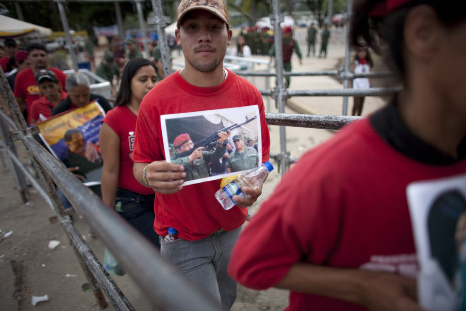 Photo - People enter the military academy to see the body of Venezuela's late President Hugo Chavez lying in state in Caracas, Venezuela, Sunday, March 10, 2013. Chavez died on March 5 after a nearly two-year bout with cancer. He was 58. (AP Photo/Ariana Cubillos)