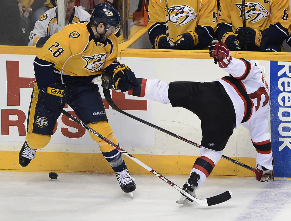 Photo - Nashville Predators forward Paul Gaustad (28) checks New Jersey Devils defenseman Andy Greene (6) into the boards while trying to get control of the puck in the first period of an NHL hockey game on Friday, Jan. 31, 2014, in Nashville, Tenn. (AP Photo/Mark Zaleski)
