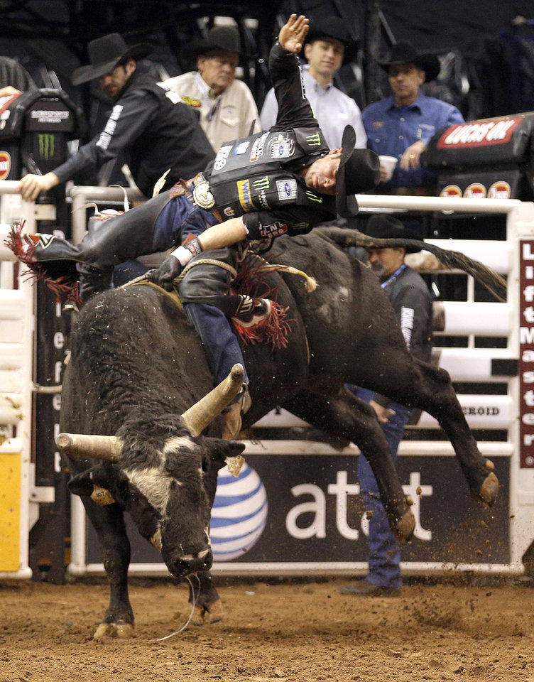Photo - Robson Palermo rides Rock & Roll during the Express Employment Professionals Invitational PBR  event at the Chesapeake Energy Arena in Oklahoma City, SUnday, Jan. 26, 2014.  Photo by Sarah Phipps, The Oklahoman