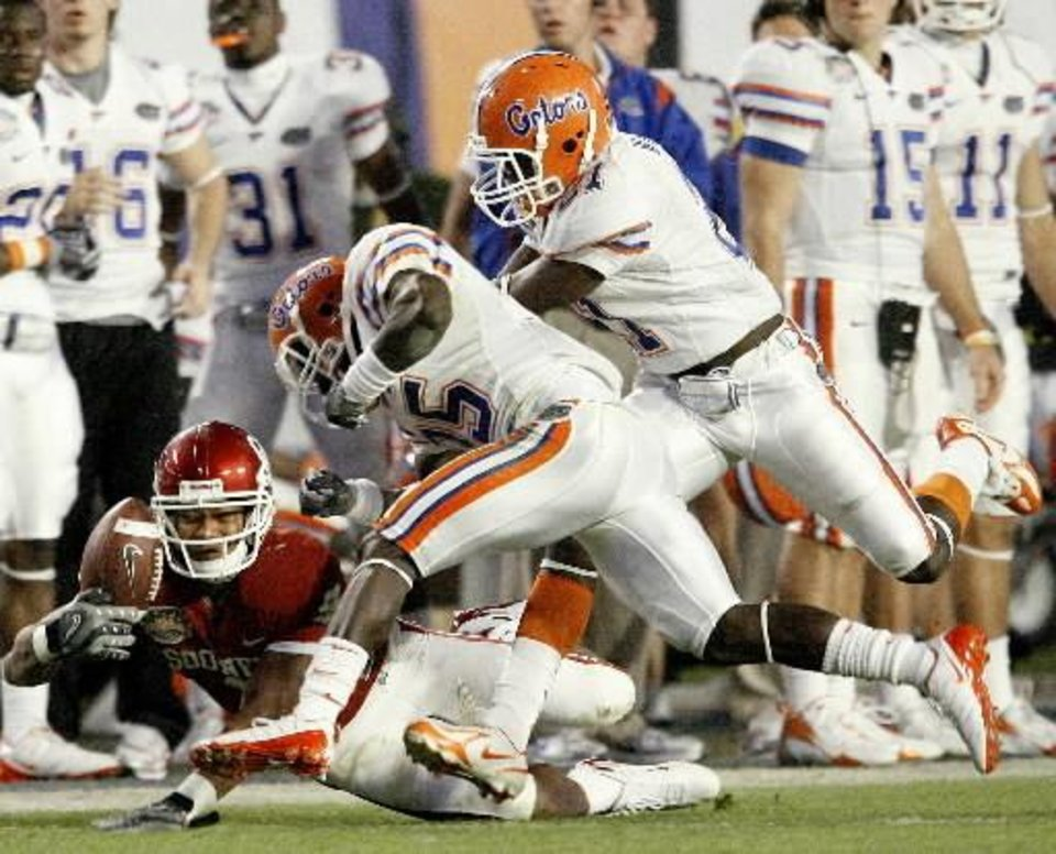 Photo - OU's Juaquin Iglesias drops a pass in front of Florida's Ahmad Black, center, and Major Wright during the second half of the BCS National Championship college football game between the University of Oklahoma Sooners (OU) and the University of Florida Gators (UF) on Thursday, Jan. 8, 2009, at Dolphin Stadium in Miami Gardens, Fla. PHOTO BY  BRYAN  TERRY