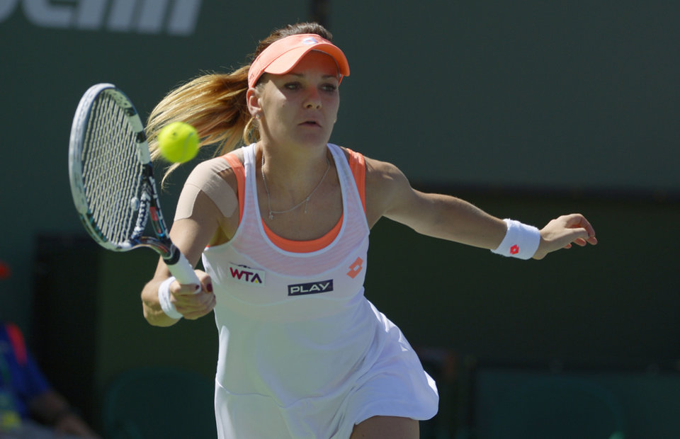 Photo - Agnieszka Radwanska, of Poland, returns a shot from Flavia Pennetta, of Italy, in their final round at the BNP Paribas Open tennis tournament, Sunday, March 16, 2014, in Indian Wells, Calif. (AP Photo/Mark J. Terrill)