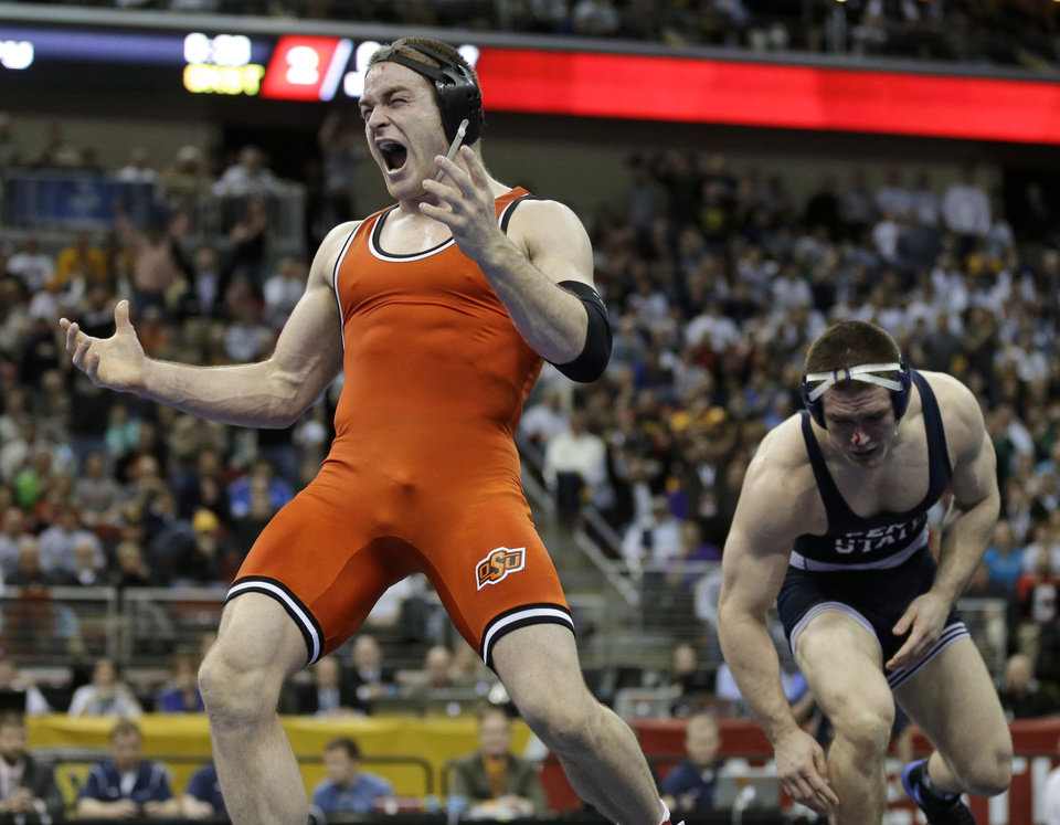 Photo - Oklahoma Stateís Chris Perry, left, reacts after defeating Penn State's Matt Brown in the 174-pound title match at the NCAA Division I wrestling championships, Saturday, March 23, 2013, in Des Moines, Iowa. (AP Photo/Charlie Neibergall)