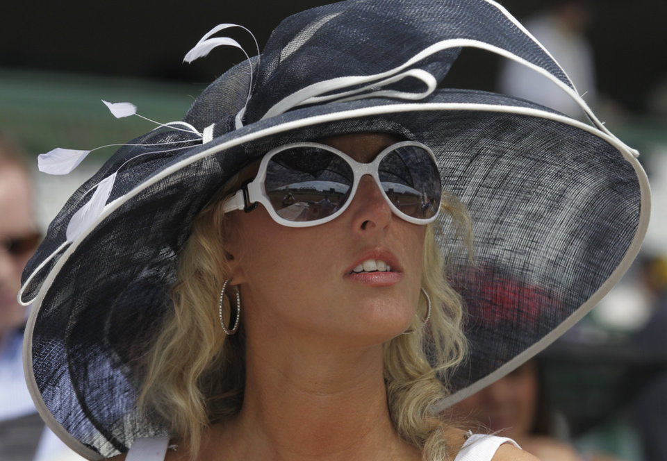 Stephanie Harris, from Lexington, KY., waits for the start of a race in the grand stand before the 138th Kentucky Derby horse race at Churchill Downs Saturday, May 5, 2012, in Louisville, Ky. (AP Photo/Michael Conroy)  ORG XMIT: DBY131