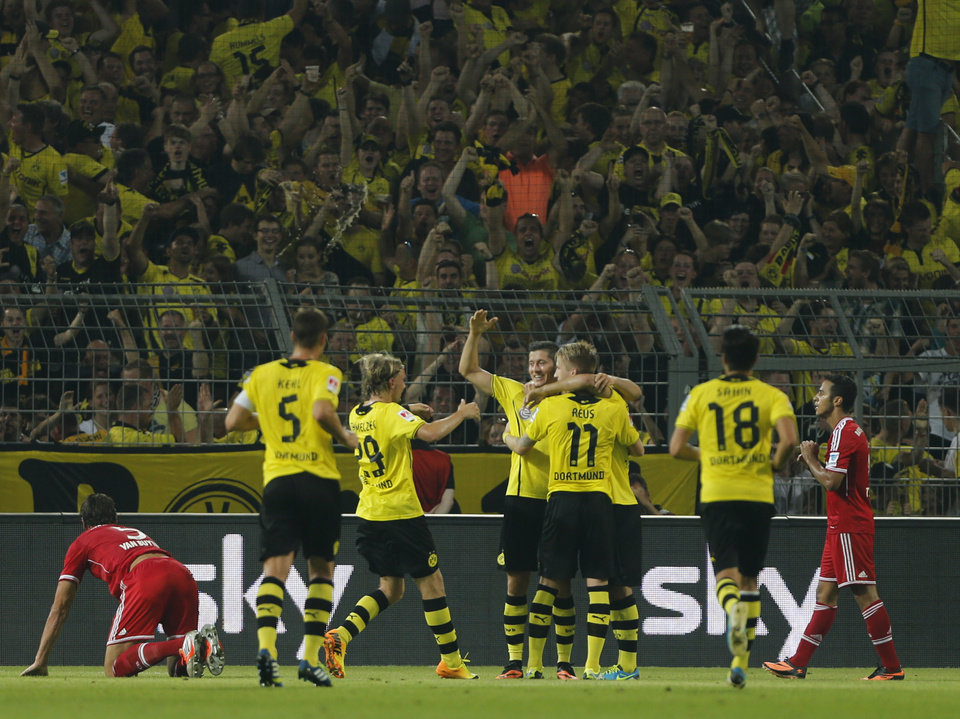 Dortmund teammates  celebrate after scoring during the Supercup final soccer match between BvB Borussia Dortmund  and Bayern Munich in Dortmund, Germany, Saturday, July 27, 2013. (AP Photo/Frank Augstein)