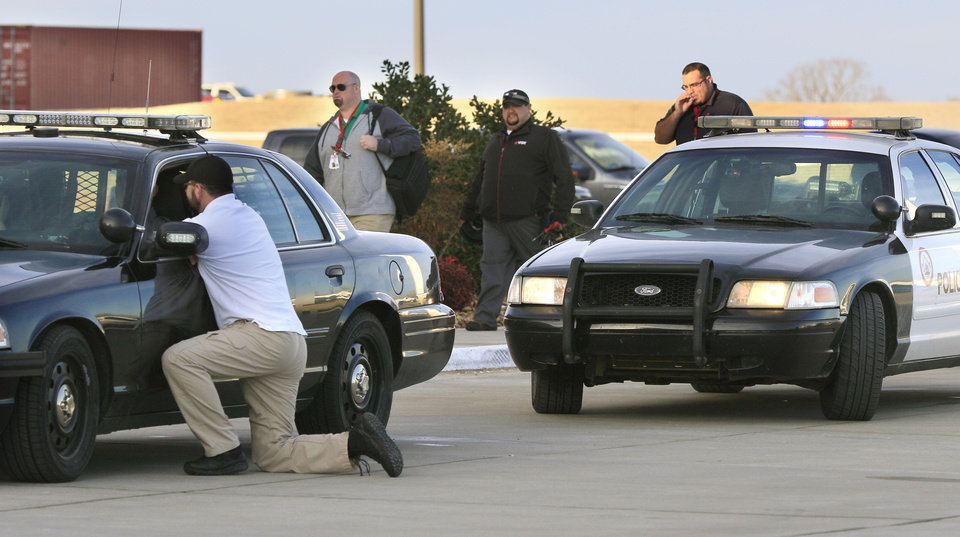 Photo -  Law officers converge at the scene of a shooting in Shawnee on Tuesday. [Photo by Paul Hellstern, The Oklahoman]