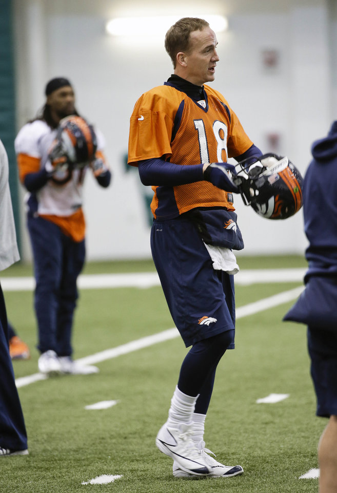 Photo - Denver Broncos quarterback Peyton Manning (18) puts his helmet on after stretching during practice Thursday, Jan. 30, 2014, in Florham Park, N.J. The Broncos are scheduled to play the Seattle Seahawks in the NFL Super Bowl XLVIII football game Sunday, Feb. 2, in East Rutherford, N.J. (AP Photo)