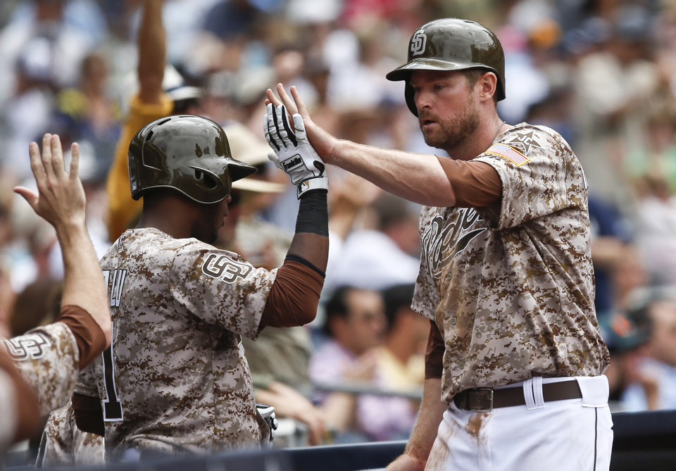 Photo - San Diego Padres' Chase Headley high fives his way into the dugout after scoring on a double by Cameron Maybin during the fourth inning of a baseball game  Sunday, June 29, 2014, in San Diego.  (AP Photo/Lenny Ignelzi)