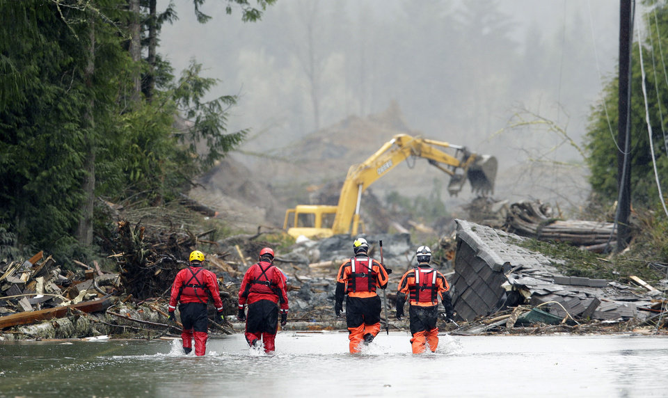Photo - Four search and rescue workers wade through water covering Washington Highway 530 Thursday, March 27, 2014, on the eastern edge of the massive mudslide that struck Saturday near Darrington, Wash. as heavy equipment moves trees and other debris in the background. (AP Photo/Ted S. Warren, Pool)