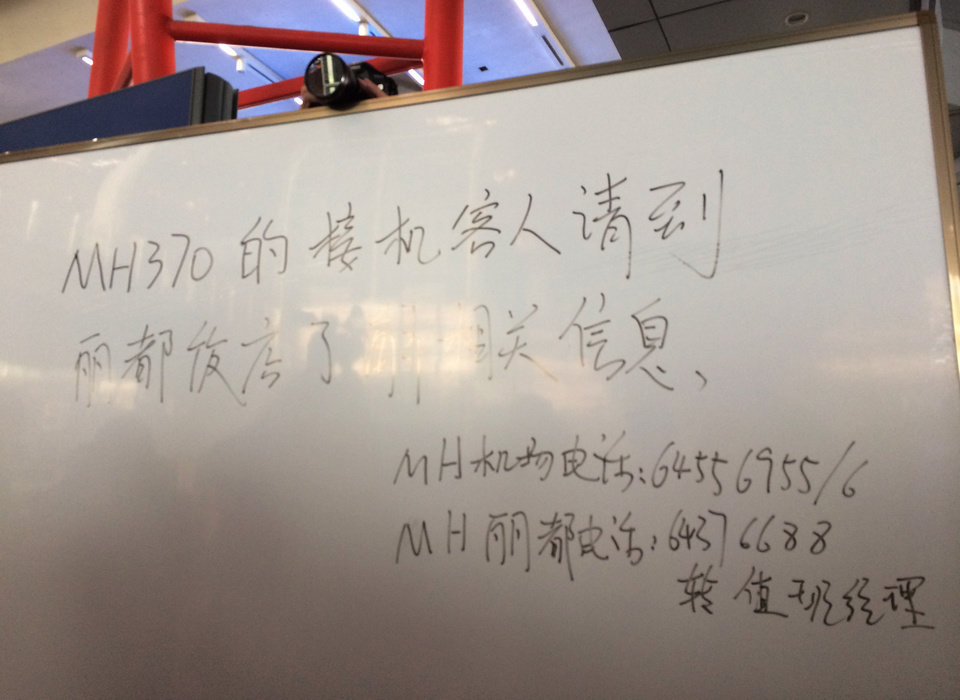Photo - This photo released by China's Xinhua News Agency, shows an notification for family members of passengers aboard flight MH370 of Malaysia Airlines that the plane is delayed, at Beijing Capital International Airport in Beijing, China on March 8, 2014.   A Malaysia Airlines Boeing 777-200 carrying 239 people lost contact with air traffic control early Saturday morning on a flight from Kuala Lumpur to Beijing, and international aviation authorities still hadn't located the jetliner several hours later. (AP Photo/Xinhua, Luo Xiaoguang) NO SALES