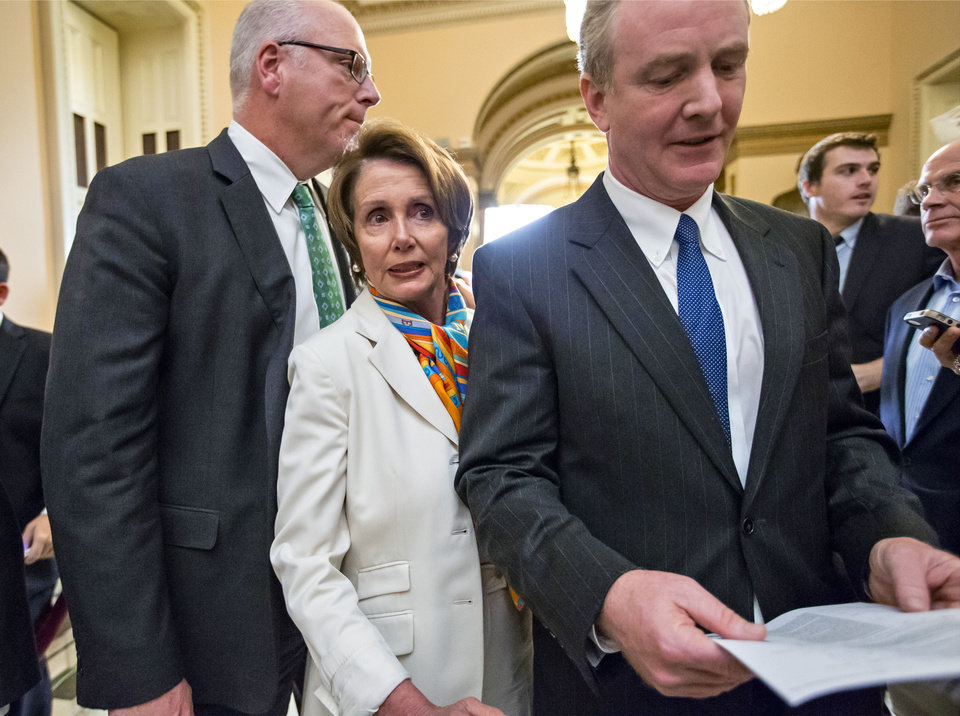 Photo - House Minority Leader Nancy Pelosi, D-Calif., center, squeezes between Rep. Joe Crowley, D-N.Y., left, and Rep. Chris Van Hollen, D-Md., right, as they return to negotiations following a news conference just before midnight at the Capitol in Washington, Monday, Sept. 30, 2013. For the first time in nearly two decades, the federal government staggered into a partial shutdown Monday at midnight after congressional Republicans stubbornly demanded changes in the nation's health care law as the price for essential federal funding and President Barack Obama and Democrats adamantly refused. (AP Photo/J. Scott Applewhite)