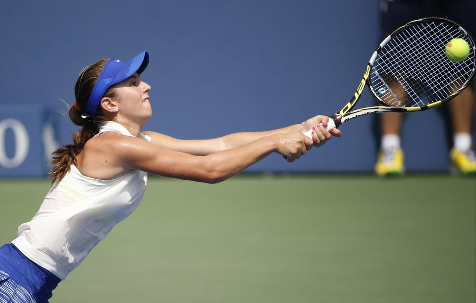 Photo - CiCi Bellis, of the United States, returns a shot against Renata Zarazua, of Mexico, during the first round of juniors play at the 2014 U.S. Open tennis tournament, Monday, Sept. 1, 2014, in New York. (AP Photo/Seth Wenig)