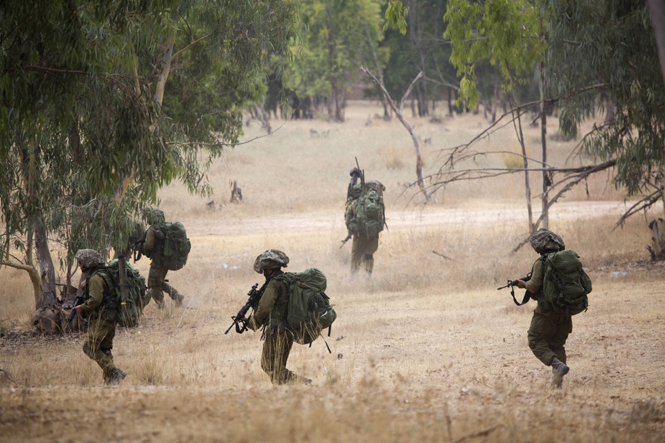 Israeli soldiers march during a drill near the Israel and Gaza border, Tuesday, July 22, 2014. Israeli airstrikes pummeled a wide range of targets in the Gaza Strip on Tuesday as the U.N. chief and the U.S. secretary of state began an intensive effort to end more than two weeks of fighting that has killed hundreds of Palestinians and dozens of Israelis. (AP Photo/Dusan Vranic)