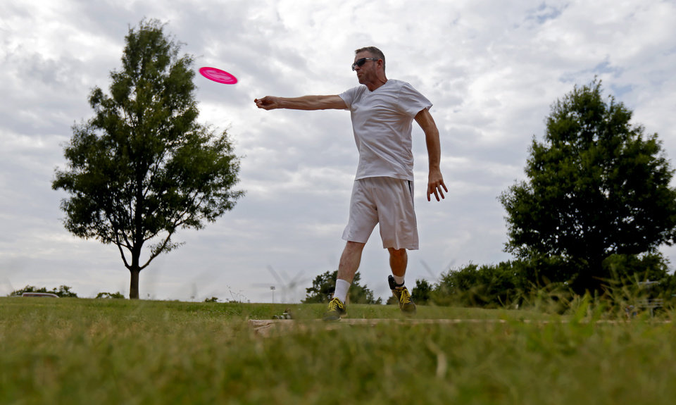 Photo -  Jason Thole plays disc golf at Will Rogers Park on Thursday, July 2, 2015. [Bryan Terry/The Oklahoman]