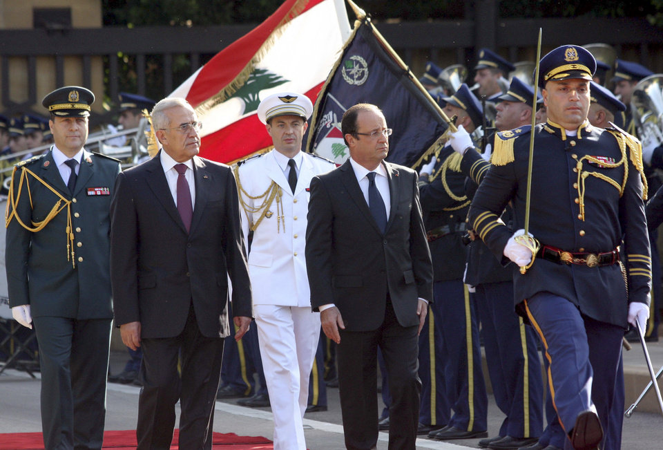 In this photo released by Lebanon's official government photographer Dalati Nohra, Lebanese President Michel Suleiman, second left, and French President Francois Hollande, second right, review honor guards, at the Presidential Palace in Baabda, east of Beirut, Lebanon, Sunday, Nov. 4, 2012. Hollande said France will stand against instability in Lebanon. Hollande�s comments during a short visit to Beirut come as many in Lebanon fear that Syria's civil war could spill over. Speaking to reporters after meeting President Michel Suleiman, Hollande said that amid Syria�s civil war, �we are committed to give you guarantees regarding security, stability and the unity of Lebanon.� A top anti-Syrian intelligence chief was killed in a car bomb in Beirut last month. The assassination stirred up deadly sectarian tensions in Lebanon, where Sunnis and Shiites are deeply divided over the Syrian civil war, raising the specter of renewed sectarian fighting. (AP Photo/Dalati Nohra)