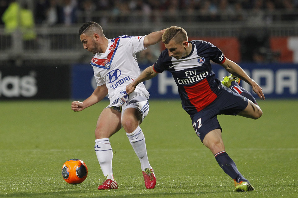 Photo - Lyon's Jordan Ferri, left, challenges for the ball with Paris Saint Germain's Lucas Digne, right, during their French League One soccer match in Lyon, central France, Sunday, April 13, 2014. (AP Photo/Laurent Cipriani)