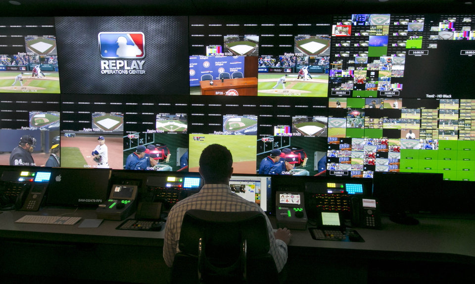 Photo - A technician works in front of a bank of television screens during a preview of Major League Baseball's Replay Operations Center, in New York, Wednesday, March 26, 2014.  Less than a week before most teams open, MLB is working on the unveiling of its new instant replay system, which it hopes will vastly reduce incorrect calls by umpires. (AP Photo/Richard Drew)
