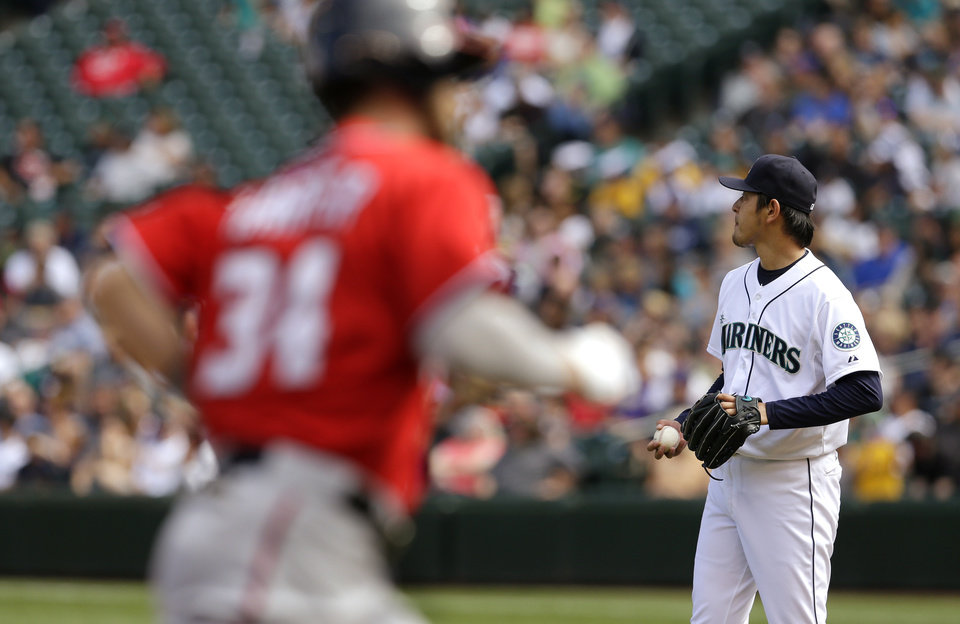 Photo - Seattle Mariners starting pitcher Hisashi Iwakuma, right, stands on the mound Washington Nationals' Bryce Harper, left, rounds the bases in the fourth inning after Harper hit his second solo home run off him in a baseball game on Sunday, Aug. 31, 2014, in Seattle. (AP Photo/Ted S. Warren)