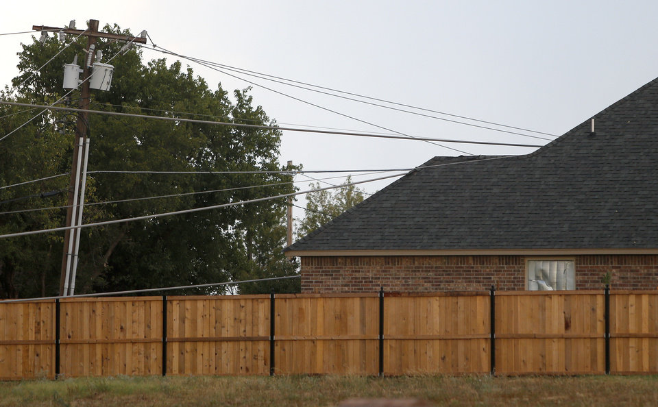 Photo - Power lines rest on a house near NW 164 and MacArthur Boulevard in Oklahoma City after storms moved through the area on Tuesday, August 7, 2012. Photo by Bryan Terry, The Oklahoman