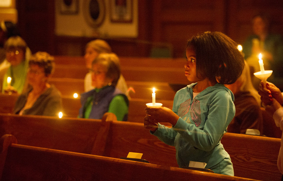Photo - Karilyn Coates, 10, joins others in a candlelight vigil for the more than 300 girls abducted by Boko Haram in Nigeria, at All Souls Unitarian Church in Colorado Springs, Colo., Thursday, May 8, 2014. More than 250 girls are still missing, and U.S. officials and agents are arriving in Nigeria to help the government rescue them. (AP Photo/The Colorado Springs Gazette, Mark Reis) MAGS OUT