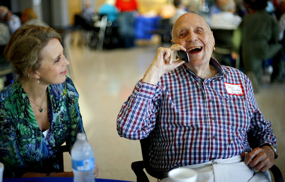 Photo - Sam Anderson watches her father, retired Col. John R. Burks laugh, as he talks on the phone with his friend, retired Brig. Gen. David Cole as the pair wait for the start of an Oklahoma Honor Flight send-off ceremony at Rose State College in Midwest City, Okla., Tuesday, October 7, 2014. Photo by Bryan Terry, The Oklahoman