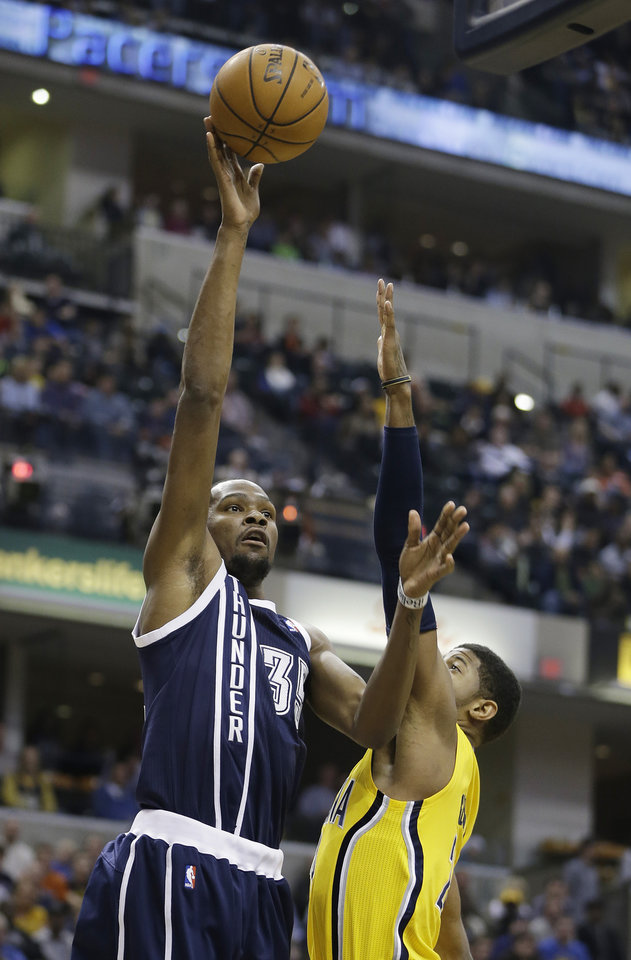 Photo - Oklahoma City Thunder's Kevin Durant, left, shoots over Indiana Pacers' Paul George during the first half of an NBA basketball game on Friday, April 5, 2013, in Indianapolis. (AP Photo/Darron Cummings)