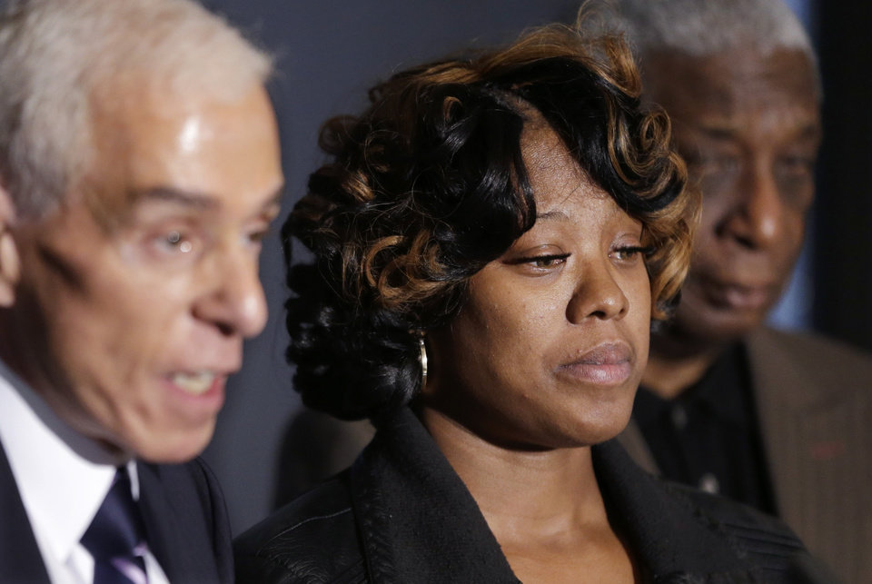 Photo - Monica McBride, center, is seen with attorney Gerald Thurswell, left, and spokesman Ron Scott, right, during a news conference in Southfield, Mich., Friday, Nov. 15, 2013. Monica's daughter, Renisha McBride, was shot on Nov. 2  in the face on Theodore P. Wafer's front porch in Dearborn Heights. (AP Photo/Carlos Osorio)
