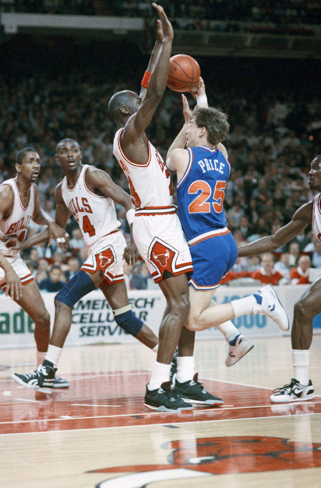 Photo - Chicago Bulls' Michael Jordan (23) stops dead in his tracks to block a shot by Cleveland Cavaliers' Mark Price (25) as Bulls' Horace Grant (54) watches during first period action, Thursday, May 3, 1989 in Chicago. (AP Photo/Mark Elias)