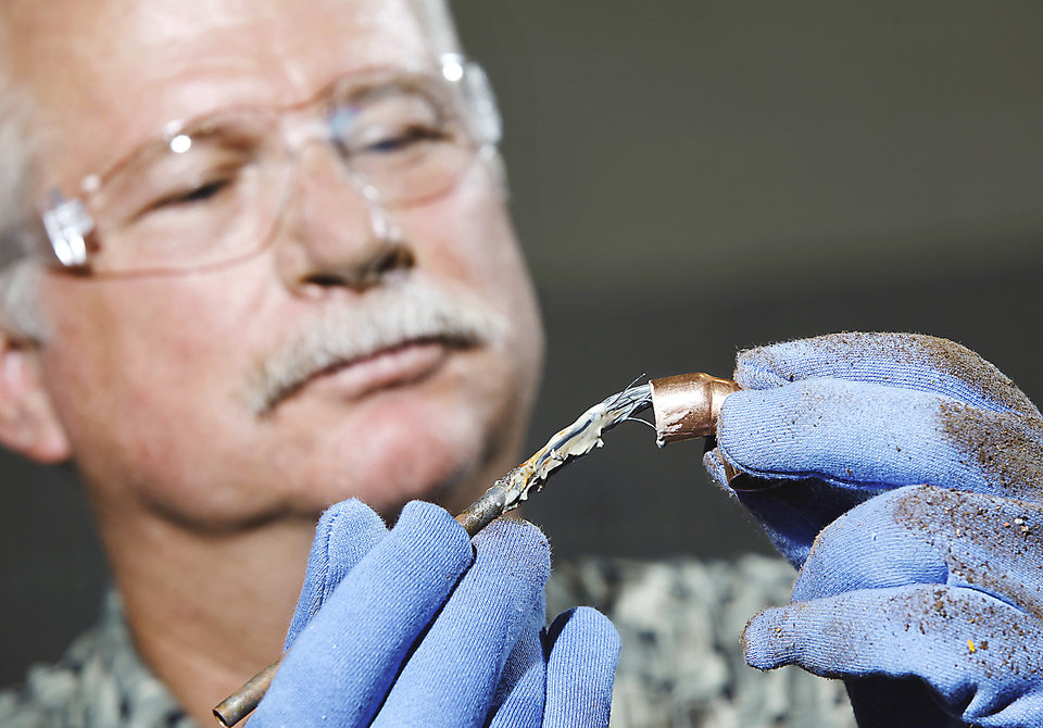 Photo - Barry Millican, a Del City High School counselor,  prepares a copper joint before it is fitted into a pipe assembly.