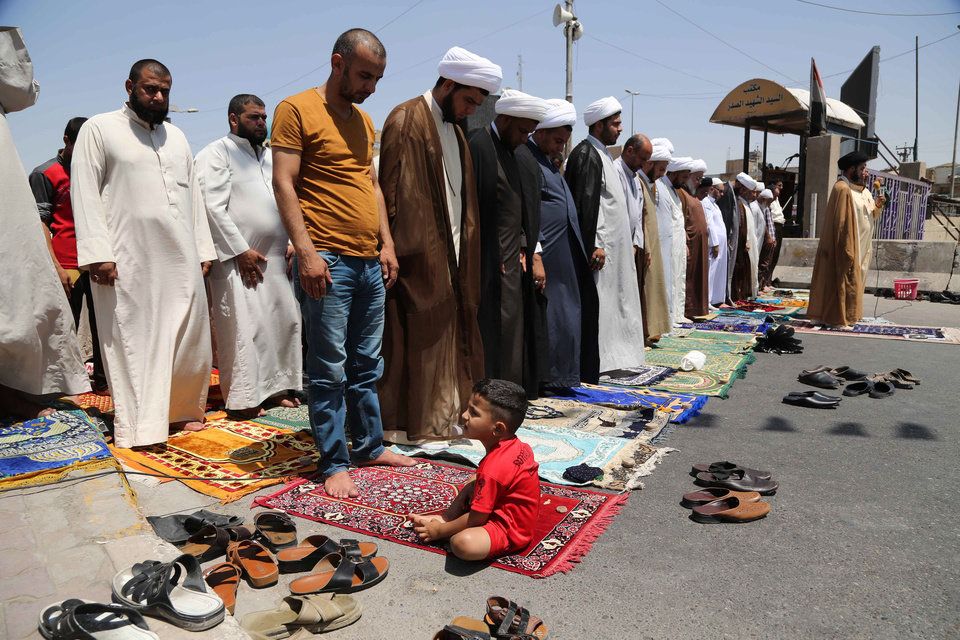 Photo - Followers of Shiite cleric Muqtada al-Sadr attend open-air Friday prayers in the Shiite stronghold of Sadr City, Baghdad, Iraq, Friday, Aug. 8 , 2014. (AP Photo/Karim Kadim)