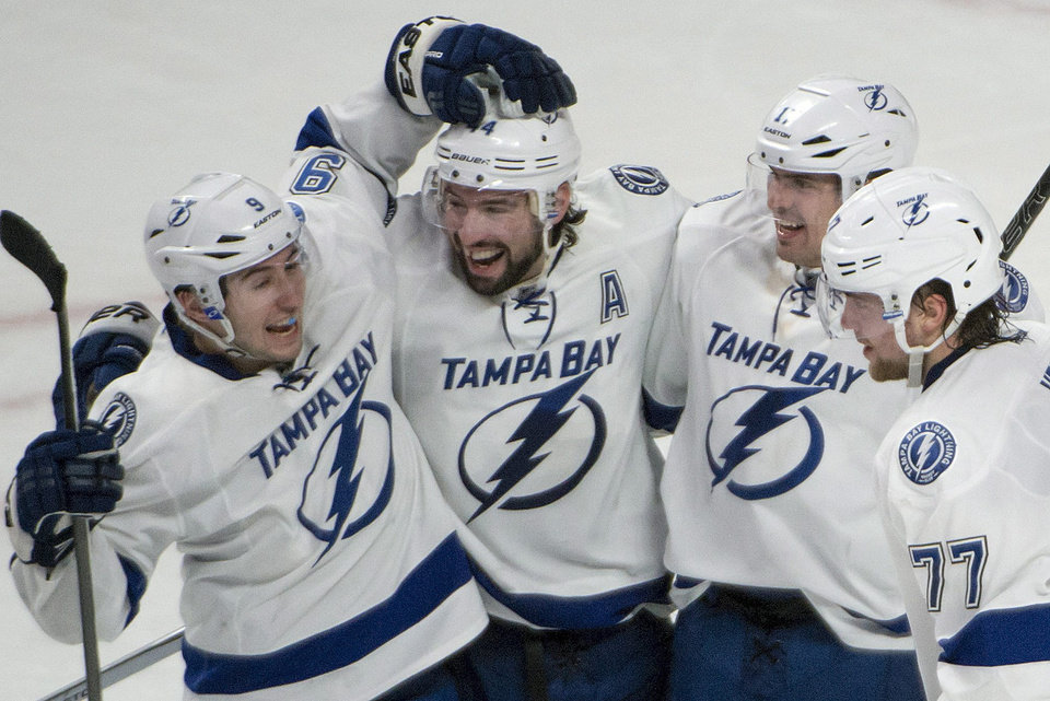 Photo - Tampa Bay Lightning Nate Thompson, second from left, celebrates his overtime goal against the Montreal Canadiens in an NHL game in Montreal, Saturday, Feb. 1, 2014. The Lightning won 2-1 in overtime. (AP Photo/The Canadian Press, Peter McCabe)