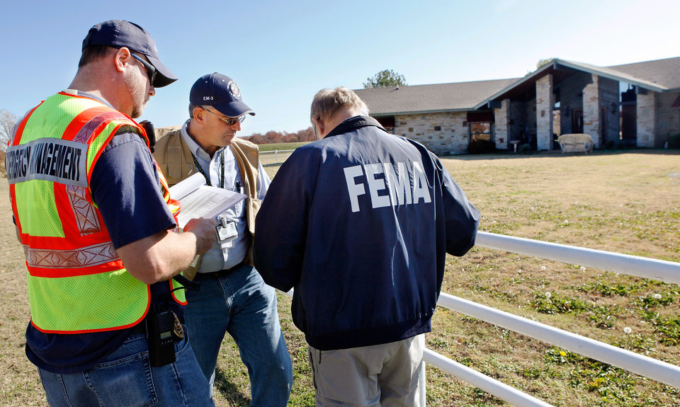 Representatives from FEMA as well as state and county emergency management teams huddle in front of Mark and Lisa Armitage's home after touring  their property Tuesday morning, Nov. 15, 2011. Several teams from these agencies  fanned across Lincoln County to assess damage from earthquakes earlier this month. The Armitage's  house sustained structural damage and the bricks of the chimney on the interior of their home fell to the floor. Workers are still dismantling the rest of the chimney so it can be rebuilt. Their home is  on US 62, about 6 miles west of Prague in rural Lincoln County. Photo by Jim Beckel, The Oklahoman