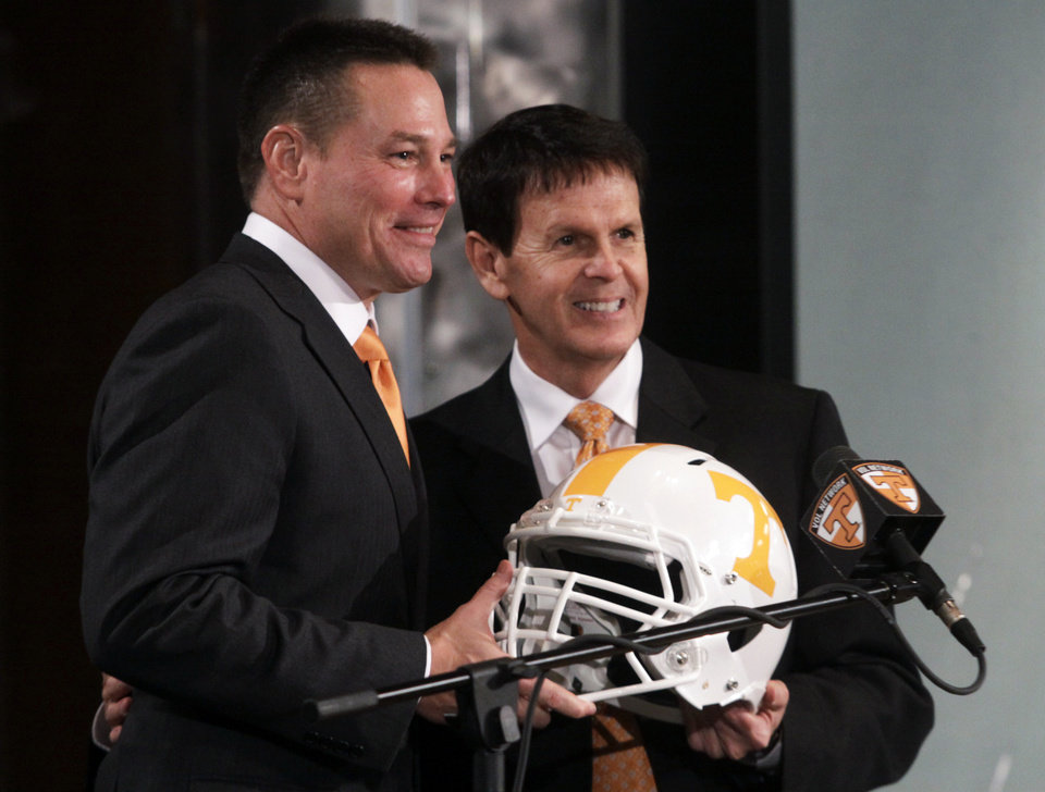 Photo - Butch Jones, left, newly-named football coach for the University of Tennessee, holds a helmet with athletic director Dave Hart during a news conference, Friday, Dec. 7, 2012, in Knoxville, Tenn. Jones replaced Derek Dooley after a 19-day coaching search. (AP Photo/Chattanooga Times Free Press, Patrick Smith) THE DAILY CITIZEN OUT; NOOGA.COM OUT; CLEVELAND DAILY BANNER OUT; LOCAL INTERNET OUT