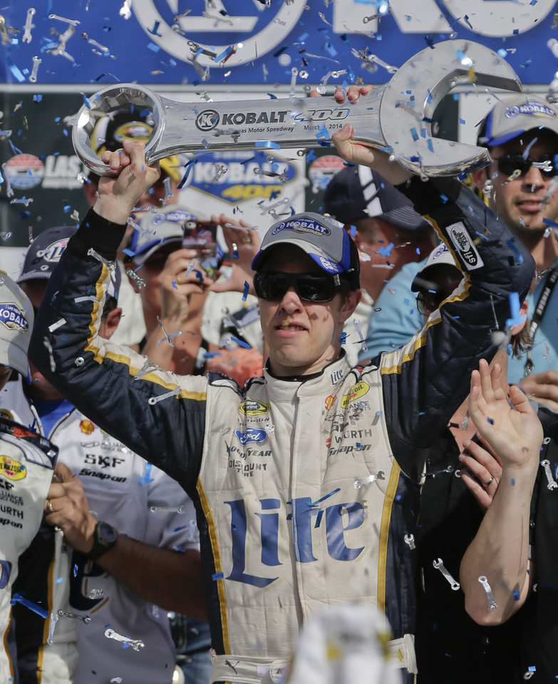Photo - Brad Keselowski holds up the Kobalt 400 trophy after winning a NASCAR Sprint Cup Series auto race on Sunday, March 9, 2014, in Las Vegas. Keselowski overtook Dale Earnhardt Jr. on the last lap when Earnhardt ran out of fuel. (AP Photo/Julie Jacobson)