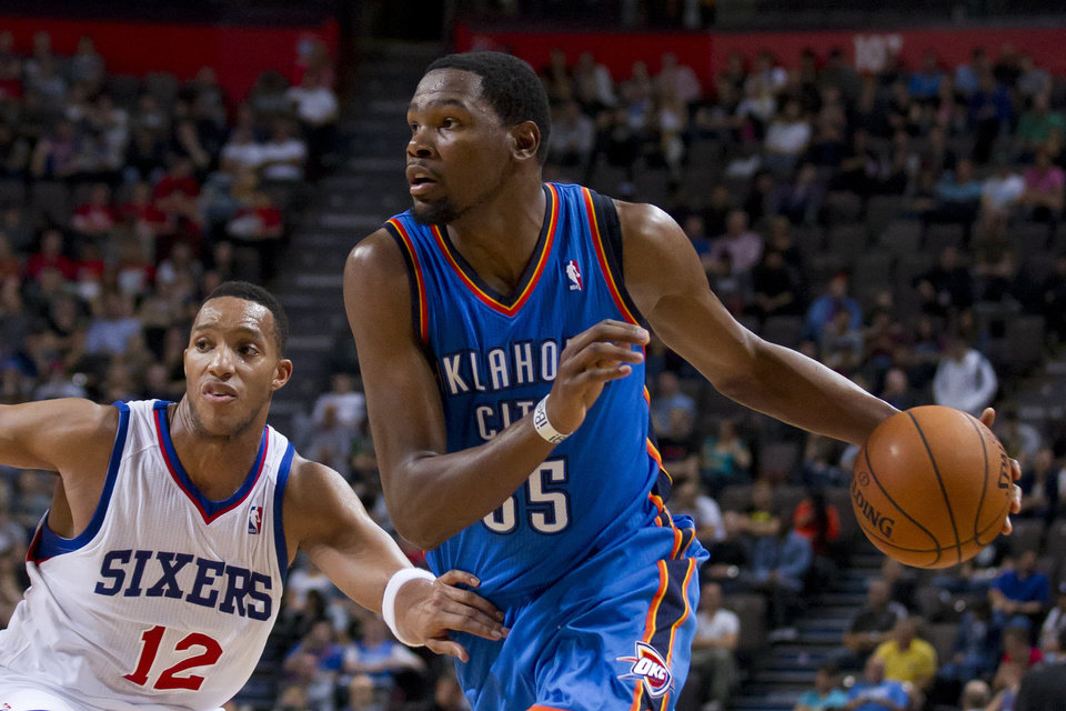 Oklahoma City Thunder\'s Kevin Durant, right, keeps the ball from Philadelphia 76ers\' Evan Turner during their NBA preseason basketball game at the Phones4 u Arena in Manchester, England, Tuesday, Oct. 8, 2013. (AP Photo/Jon Super) ORG XMIT: MJS112