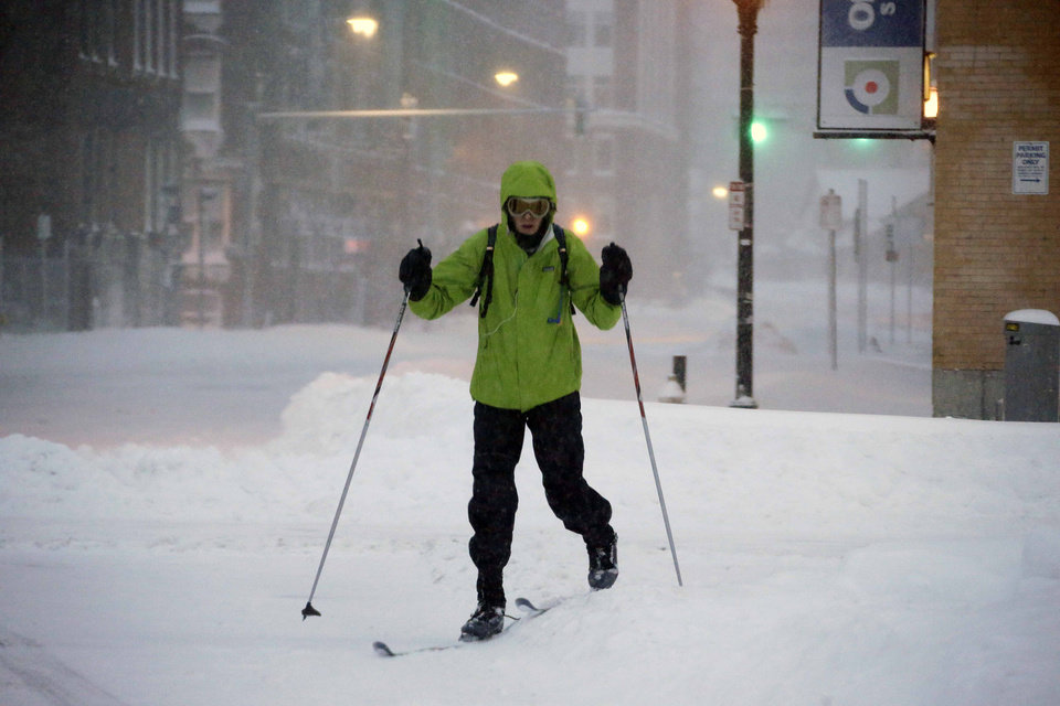 Photo - A pedestrian uses skis to travel through the deserted snow-covered streets of Boston early Saturday, Feb. 9, 2013. (AP Photo/Gene J. Puskar)
