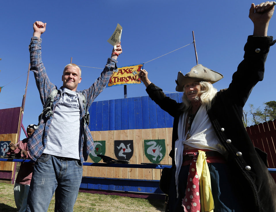 Photo -  Left: Jamie Flowers celebrates his toss at the Axe Throw with Pirate One Eye, aka Ron Neal, at the Medieval Fair on Friday at Reaves Park in Norman. PHOTOs BY STEVE SISNEY, THE OKLAHOMAN   STEVE SISNEY -