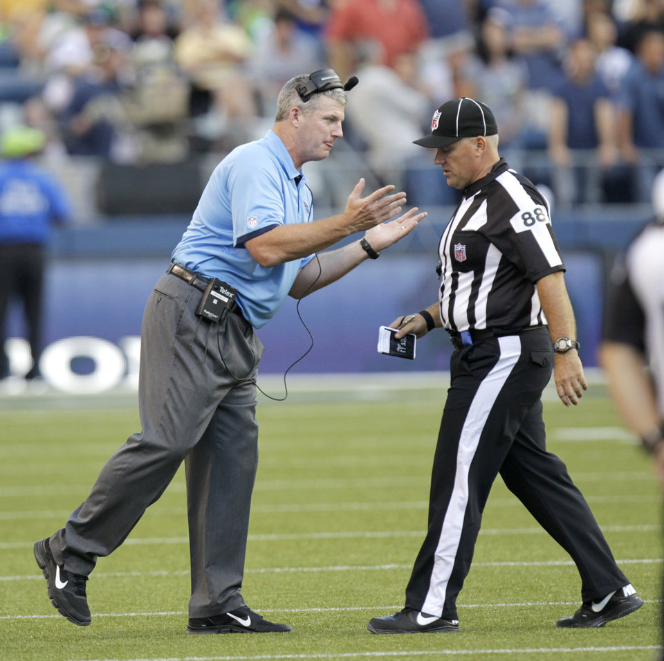 Photo -   FILE - This Aug. 11, 2012 file photo, shows Tennessee Titans head coach Mike Munchak, left, arguing with a replacement official in the first half of an NFL football preseason game against the Seattle Seahawks, in Seattle. The NFL will open the regular season with replacement officials. League executive Ray Anderson has told the 32 teams that with negotiations remaining at a standstill between the NFL and the officials' union. The replacements will be on the field beginning next Wednesday night when the Cowboys visit the Giants to open the season. (AP Photo/Rick Bowmer, File)