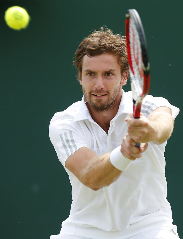 Photo - Ernests Gulbis of Latvia plays a return to to Sergiy Stakhovsky of Ukraine during their men's single match at the All England Lawn Tennis Championships in Wimbledon, London, Wednesday, June 25, 2014. (AP Photo/Ben Curtis)