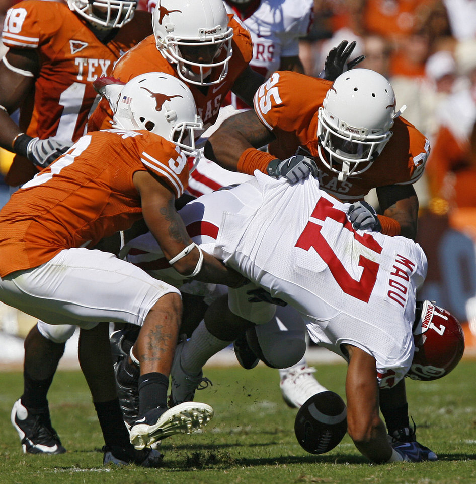 Photo - Oklahoma's Mossis Madu (17) fumbles the ball on a kick return under the pressure of the Texas coverage team during the Red River Rivalry college football game between the University of Oklahoma Sooners (OU) and the University of Texas Longhorns (UT) at the Cotton Bowl in Dallas, Texas, Saturday, Oct. 17, 2009. Photo by Chris Landsberger, The Oklahoman
