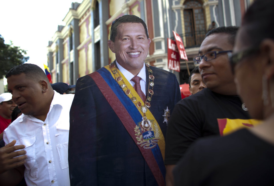 A life-size cut out image of Venezuela's President Hugo Chavez is carried by a Chavez supporter during a symbolic inauguration ceremony for Chavez in Caracas, Venezuela, Thursday, Jan. 10, 2013. The government organized the unusual show of support for the cancer-stricken leader on the streets outside Miraflores Palace on what was supposed to be Chavez's inauguration day. The Venezuelan leader, normally at the center of national attention, is so ill following a fourth cancer surgery in Cuba that he has made no broadcast statement in more than a month, and has not appeared in a single photo. Officials have not specified what sort of cancer he suffers or which hospital is treating him. (AP Photo/Ariana Cubillos)