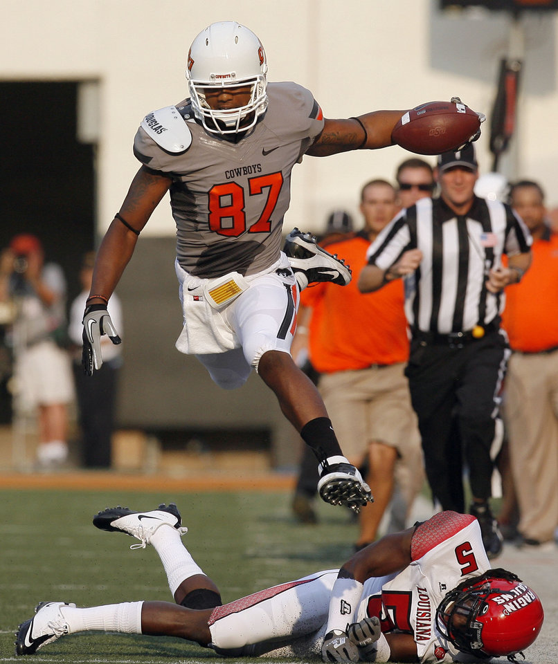 Photo - Oklahoma State's Tracy Moore leaps over Louisiana-Lafayette's Dwight Bentley during their game Saturday in Stillwater. Photo by Sarah Phipps, The Oklahoman