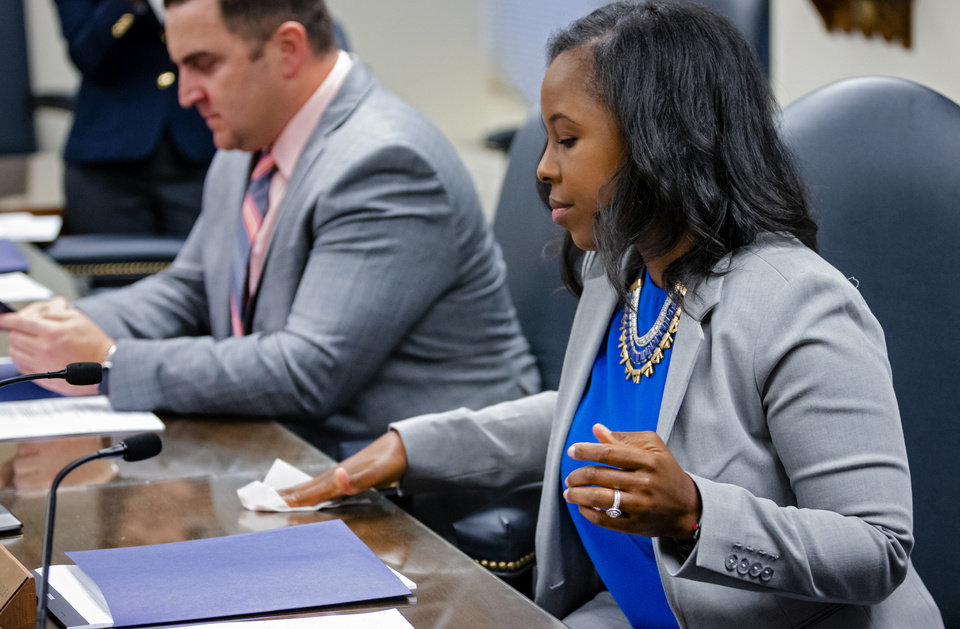 Photo - Oklahoma State Department of Education  board member Carlisha Williams Bradley wipes down the desk before the start of Oklahoma's State Superintendent of Public Instruction, Joy Hofmeister's emergency meeting of the Oklahoma State Department of Education in Oklahoma City, Okla. on Monday, March 16, 2020 to announce the closing of public school till April 6 to combat the spread of the Coronavirus.  [Chris Landsberger/The Oklahoman]
