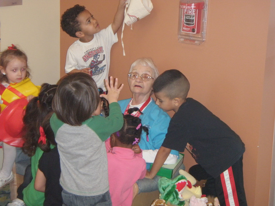 Photo -  Helen Turner, center, who has been volunteering with the Foster Grandparent Program for 16 years, sits with children during one of her volunteer shifts. Photo provided      -