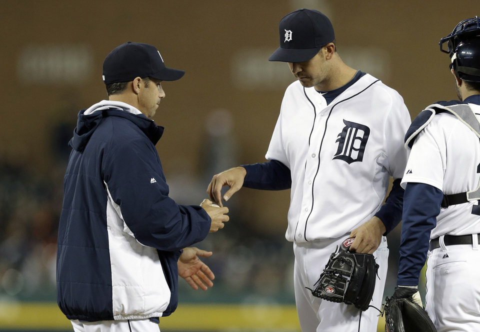 Photo - Detroit Tigers manager Brad Ausmus, left, relieves pitcher Luke Putkonen during the sixth inning of a baseball game against the Los Angeles Angels in Detroit, Friday, April 18, 2014. (AP Photo/Carlos Osorio)