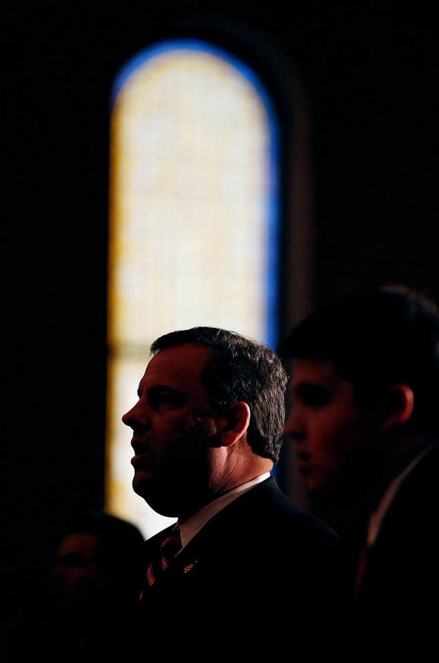 Photo - New Jersey Gov. Chris Christie is silhouetted as he attends a prayer service with his family in celebration of his inauguration at the New Hope Baptist Church on Tuesday, Jan. 21, 2014 in Newark. The celebrations to mark the start of Christie's second term could be tempered by investigations into traffic tie-ups that appear to have been ordered by his staff for political retribution and an allegation that his administration linked Superstorm Sandy aid to approval for a real estate project. (AP Photo/Rich Schultz)
