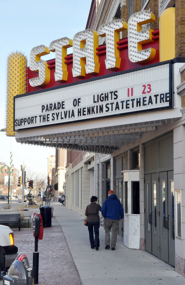 Photo -   In this Nov. 17, 2012 photo a couple walks under the marquee of the historic downtown State Theatre in Sioux Falls, S.D. The circa-1926 movie house, closed since 1991, has been raising funds for its renovation and plans to begin showing films again in 2013. (AP Photo/Dirk Lammers)